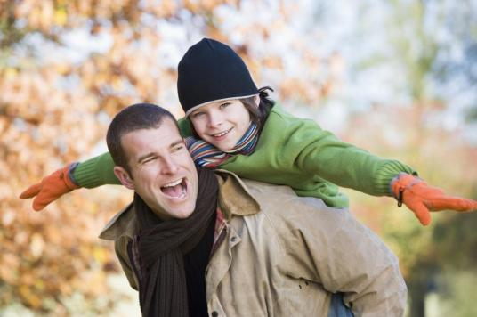 Father piggybacking son outdoors at park and smiling