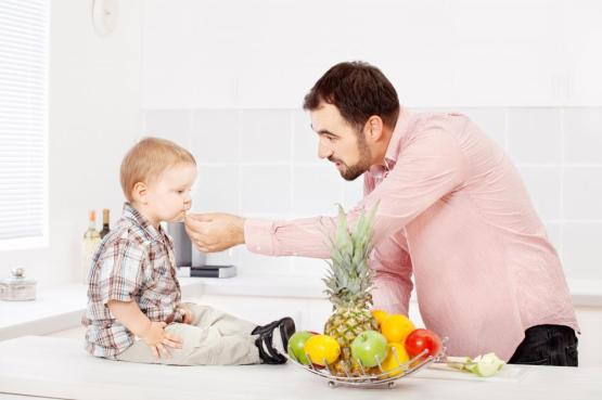 Father feeding child in kitchen