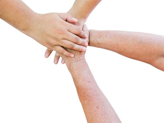 Seniors hands and young hands in unity on white background
